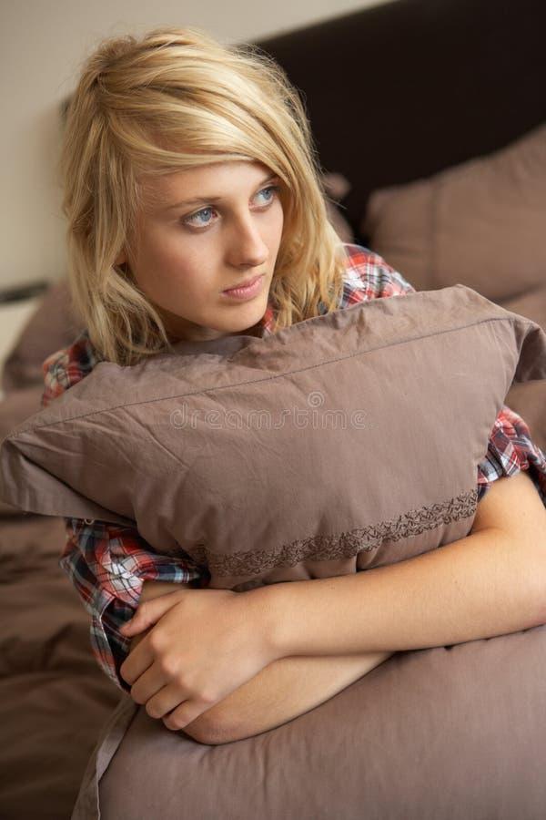拥抱枕头的卧室沮丧的女孩少年 免版税图库摄影