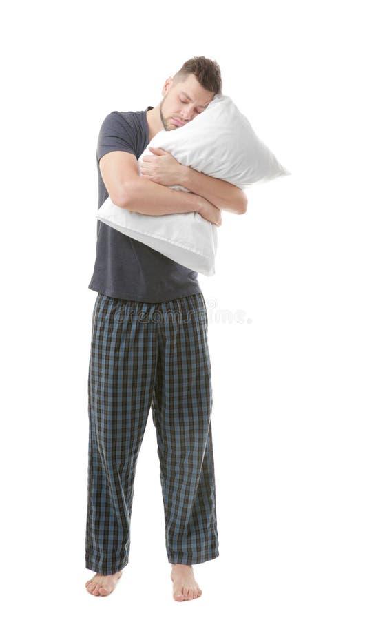 拥抱枕头的睡衣的年轻困人 免版税库存图片