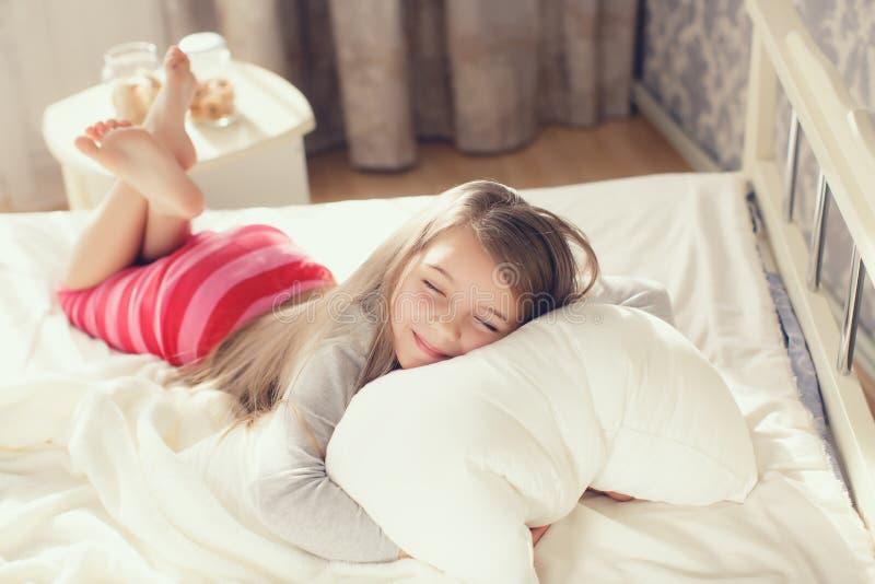 拥抱枕头的一个小女孩的画象 免版税图库摄影