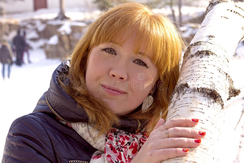 拥抱桦树的树干的红发女孩 免版税库存照片
