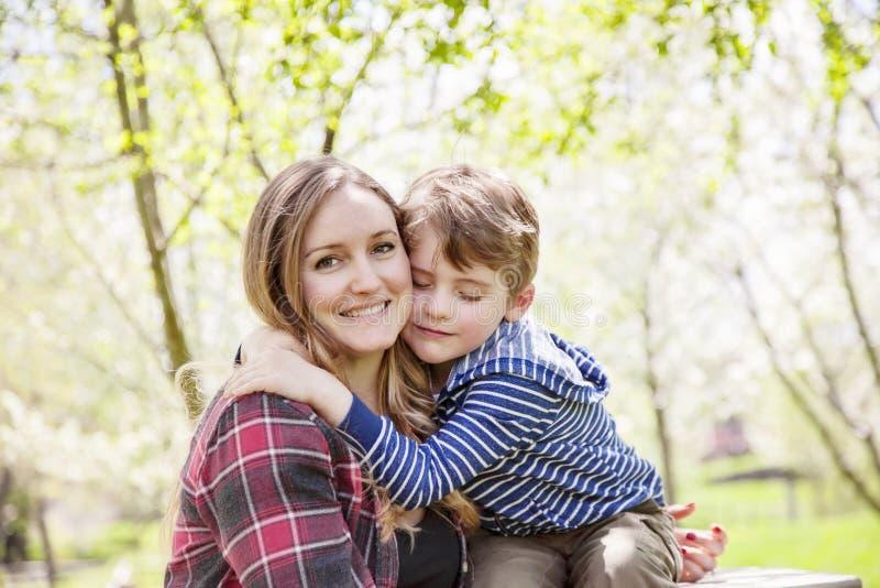 拥抱母亲外面在春天的男孩 库存照片