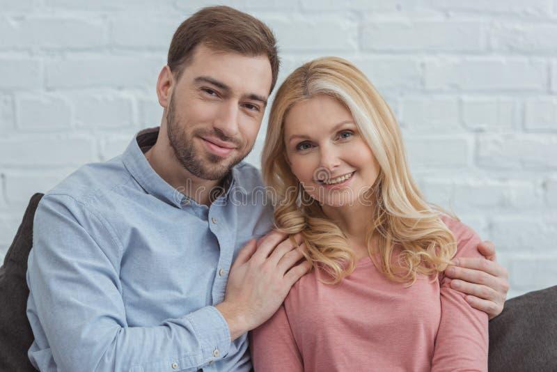 拥抱母亲的微笑的儿子画象,当基于沙发时 免版税库存图片