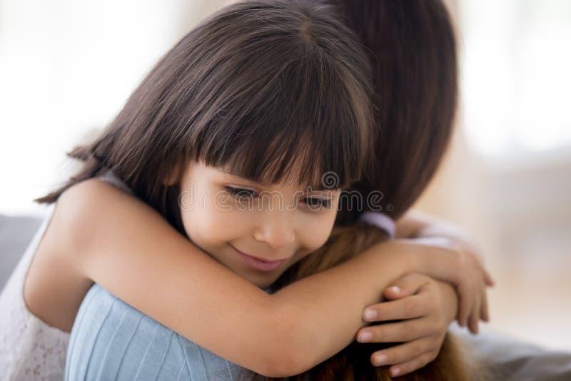 拥抱母亲的恳切的女儿表达爱和热爱 库存照片
