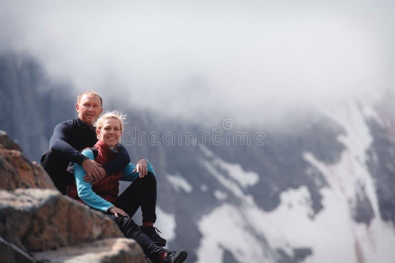 拥抱浪漫年轻愉快的夫妇亲吻和 雨和雾 在爱的年轻夫妇在山背景  库存照片
