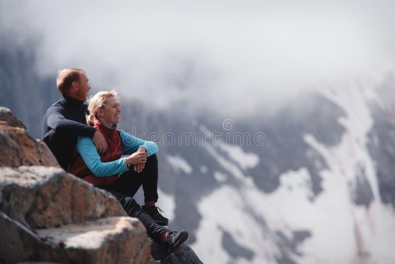 拥抱浪漫年轻愉快的夫妇亲吻和 雨和雾 在爱的年轻夫妇在山背景  库存图片