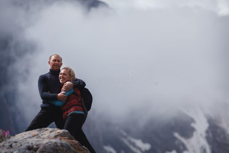 拥抱浪漫年轻愉快的夫妇亲吻和 雨和雾 在爱的年轻夫妇在山背景  免版税库存照片