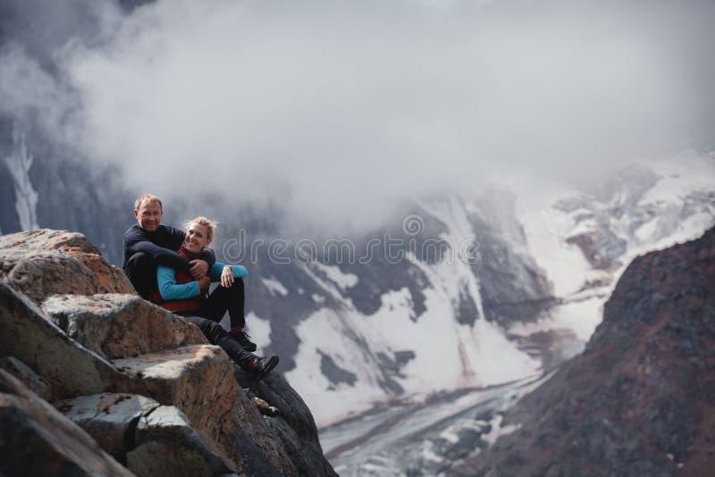 拥抱浪漫年轻愉快的夫妇亲吻和 雨和雾 在爱的年轻夫妇在山背景  免版税库存图片