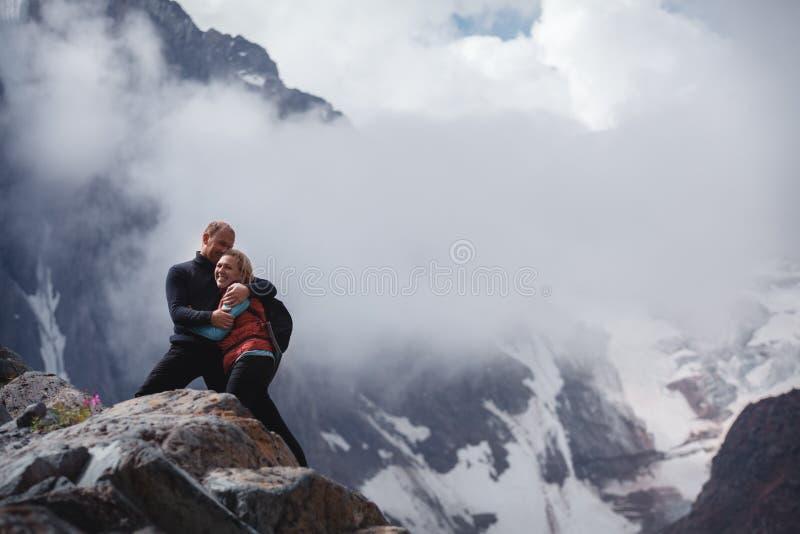 拥抱浪漫年轻愉快的夫妇亲吻和 雨和雾 在爱的年轻夫妇在山背景  图库摄影
