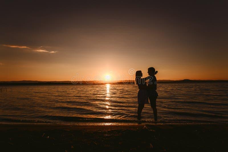 拥抱海的人和女孩在日落 免版税库存照片