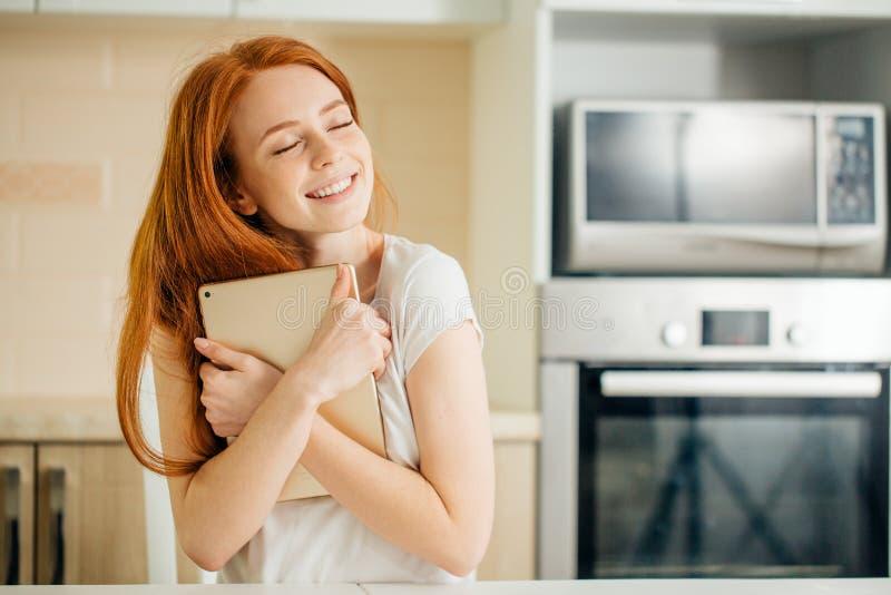 拥抱片剂和看上面在白色墙壁上的女孩 库存图片