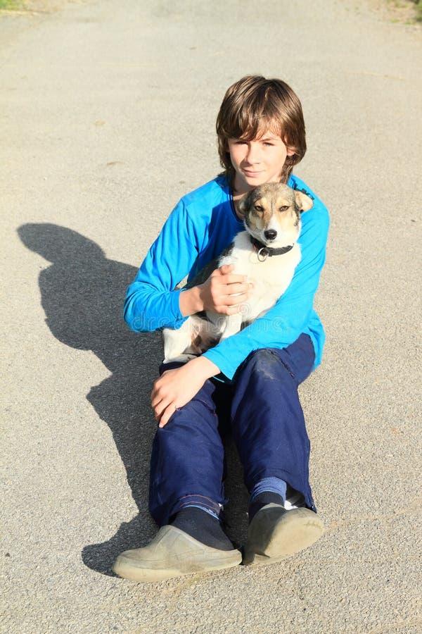 拥抱狗的小男孩 免版税库存照片