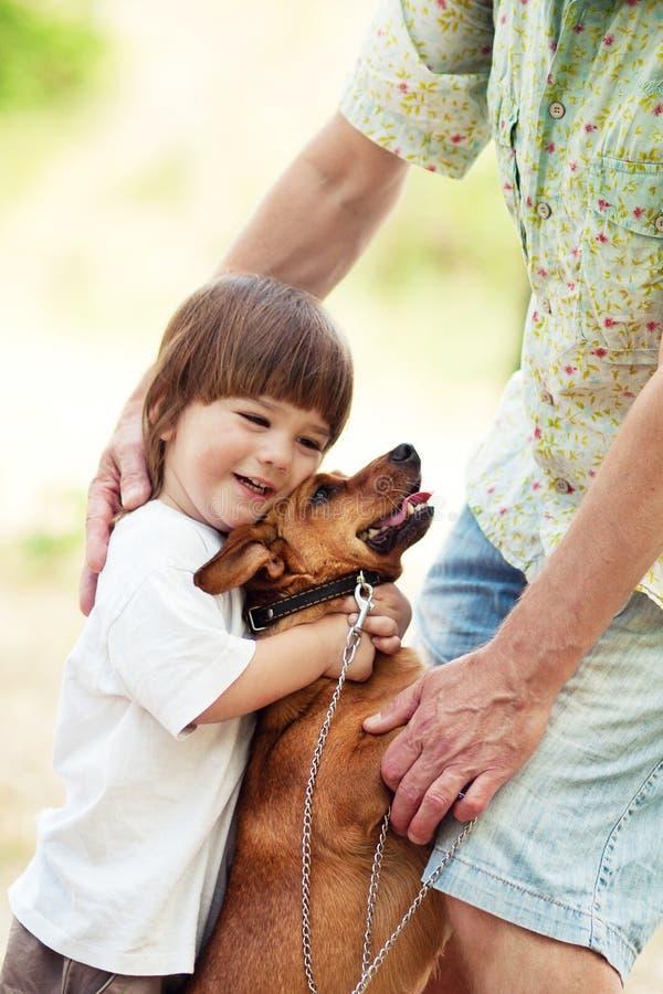 拥抱狗的逗人喜爱的男孩在与父亲的步行 图库摄影