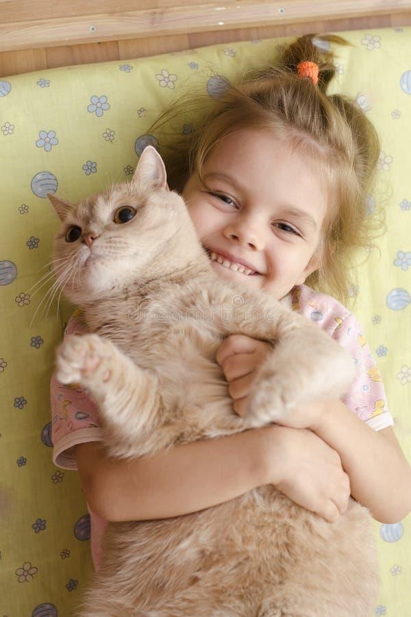 拥抱猫的小女孩说谎在地板上的床垫 库存照片