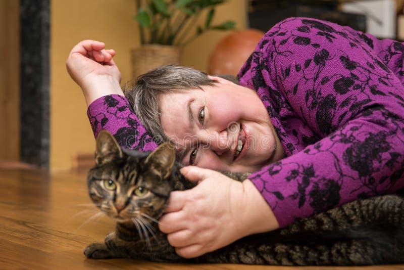 拥抱猫,动物协助的疗法的弱智的妇女 免版税库存照片