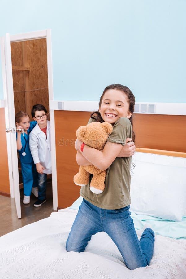 拥抱玩具熊一会儿男孩的女孩 免版税库存照片