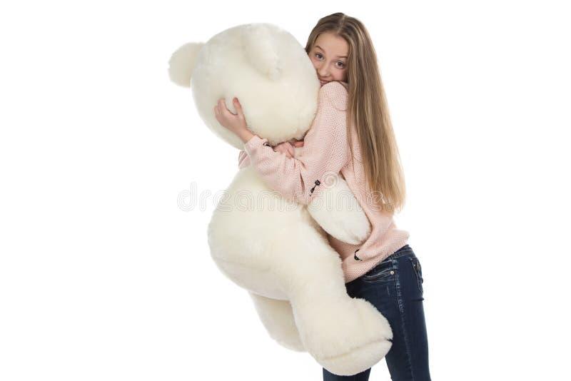 拥抱玩具熊的十几岁的女孩照片 库存图片