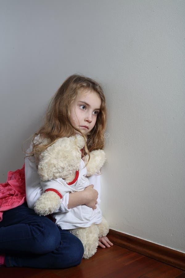 拥抱玩具熊的哀伤的女孩 免版税图库摄影