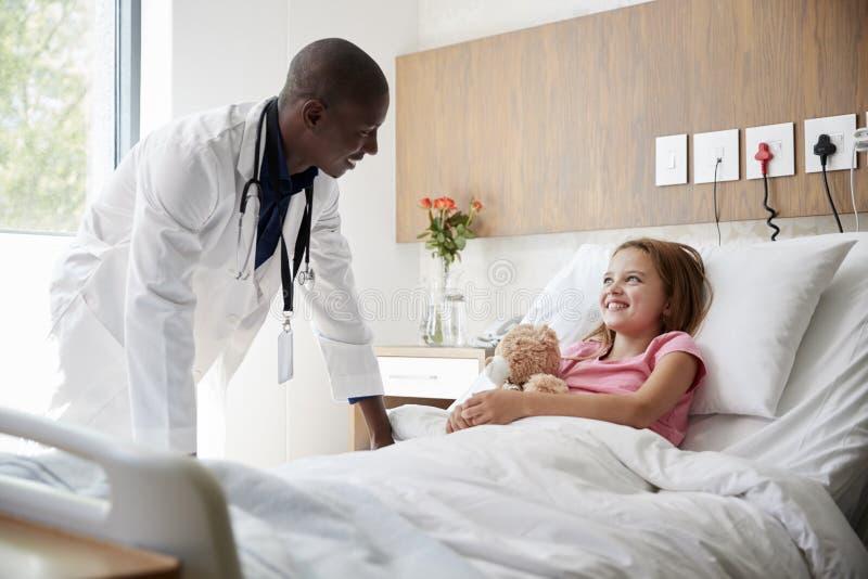 拥抱玩具熊的男性Visiting Girl Lying In医生医院病床 库存照片