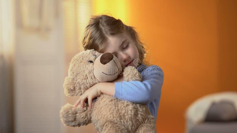 拥抱玩具熊,遭受的寂寞,家庭问题的小孤独的女孩 免版税库存照片
