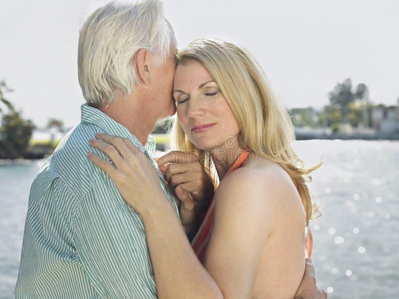 拥抱由河的夫妇 免版税库存照片