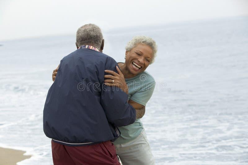 拥抱由海洋的资深夫妇 库存图片