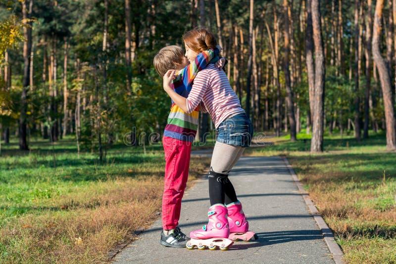 拥抱男孩的溜冰鞋的红发女孩在公园 库存照片