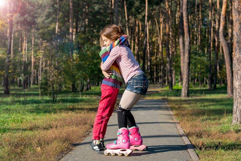 拥抱男孩的溜冰鞋的红发女孩在公园 图库摄影