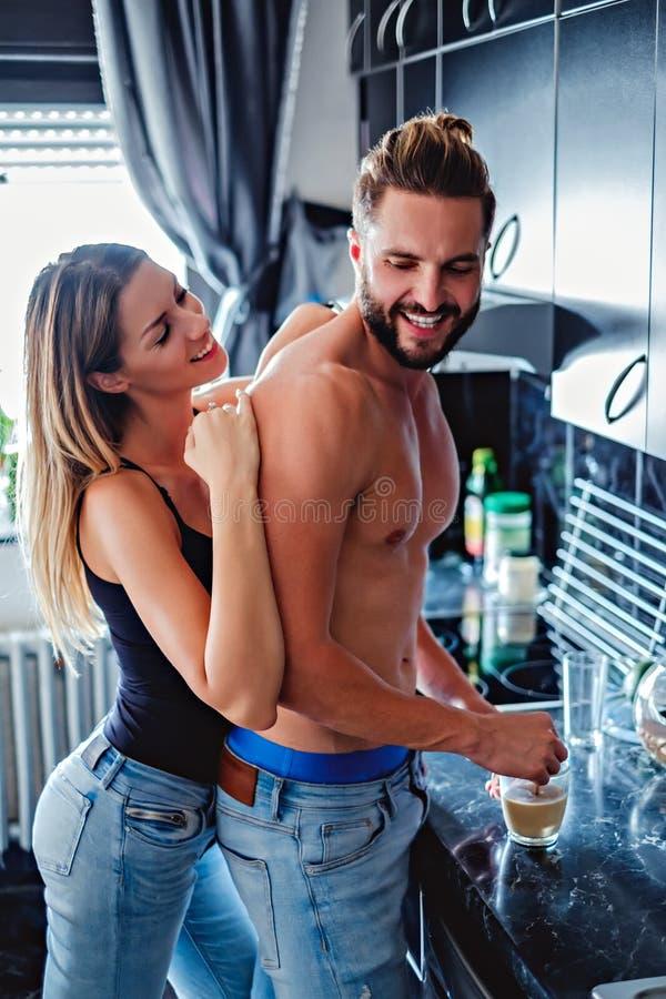 拥抱男朋友从后面的女孩,当他做咖啡时 免版税库存图片