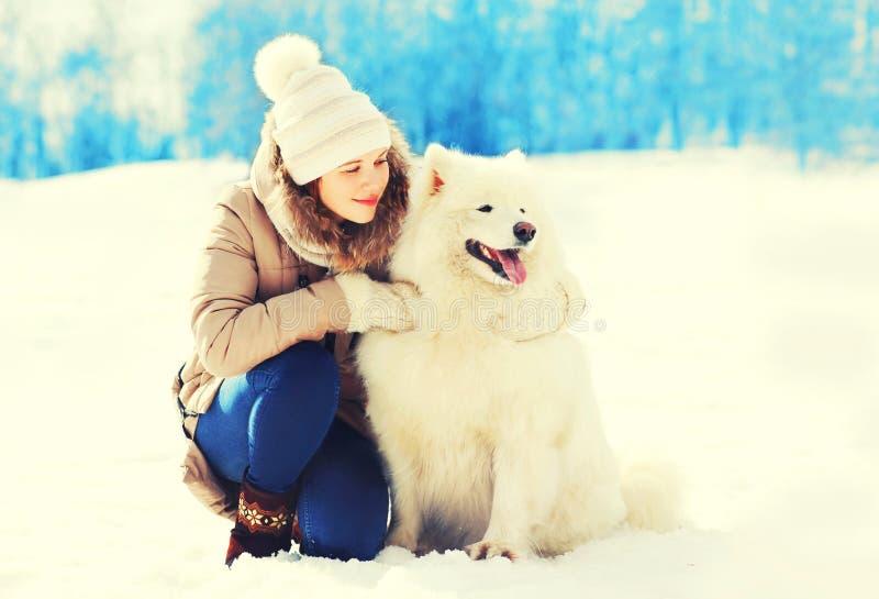 拥抱白色萨莫耶特人狗的妇女所有者在冬天 免版税库存照片