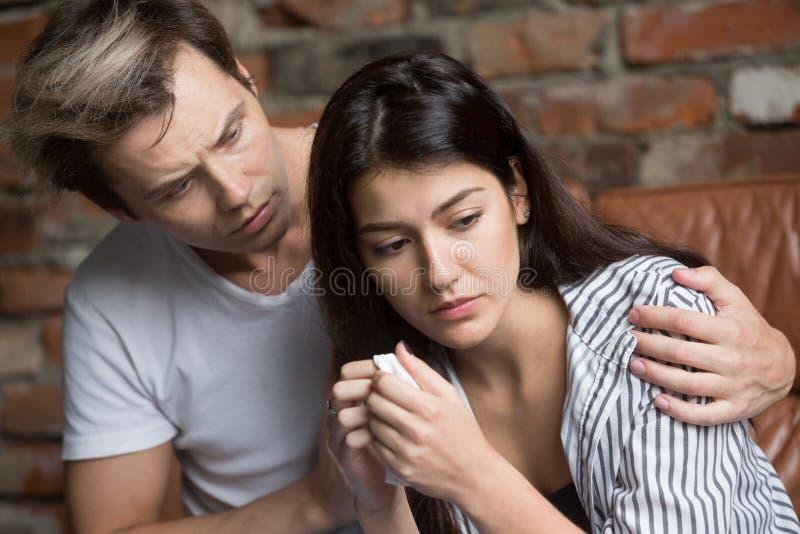 拥抱的丈夫安慰哀伤的哭泣的配偶 免版税库存图片