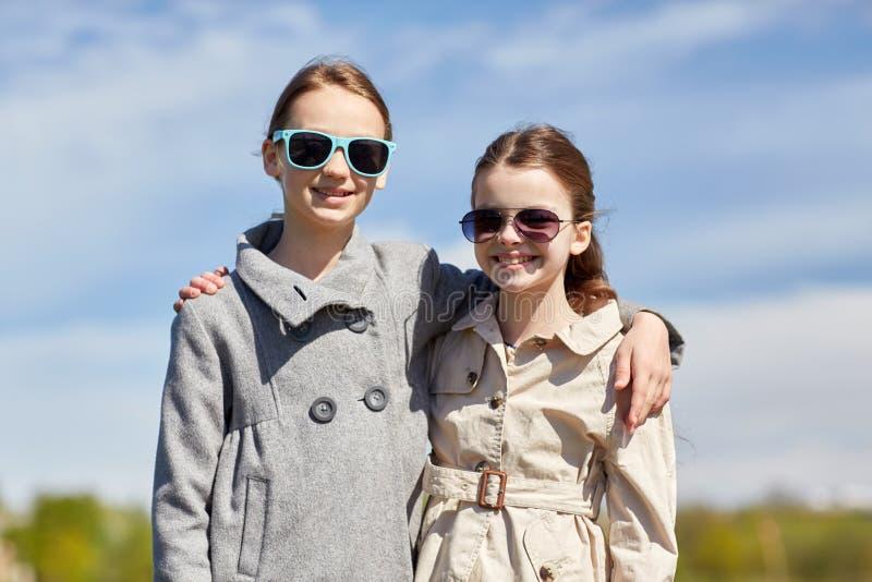 拥抱的太阳镜的愉快的小女孩户外 库存图片