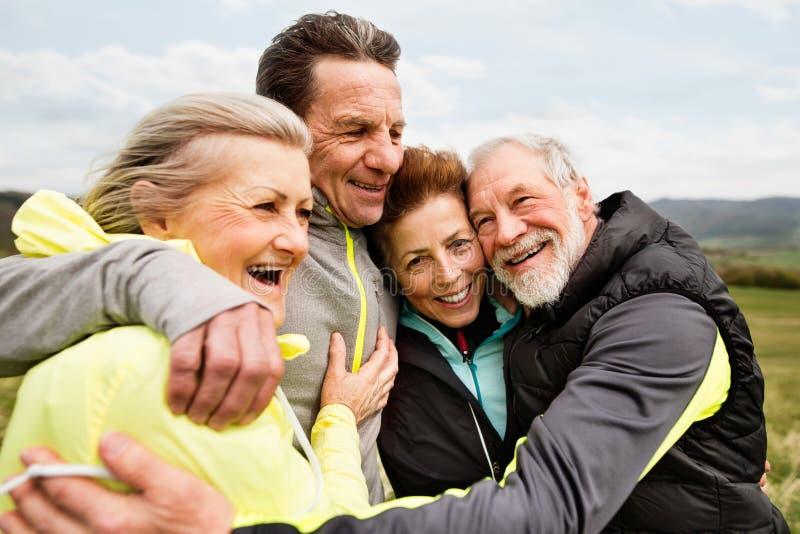 拥抱的小组户外资深赛跑者,休息和 免版税库存图片