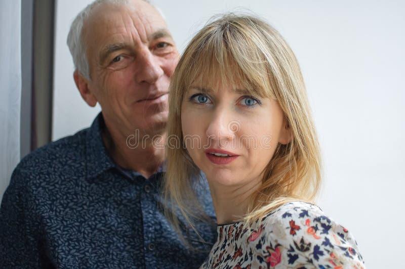 拥抱的年长人和他的年轻金发的妻子接近的画象户内 加上年龄 免版税库存照片