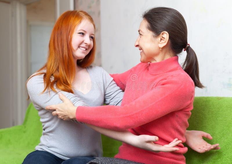 拥抱的母亲和少年女儿 免版税库存图片