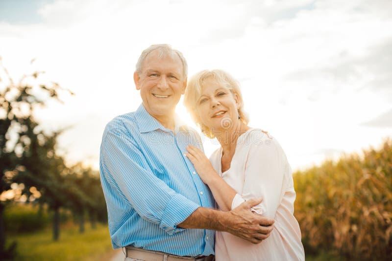 拥抱的资深夫妇户外 免版税库存照片