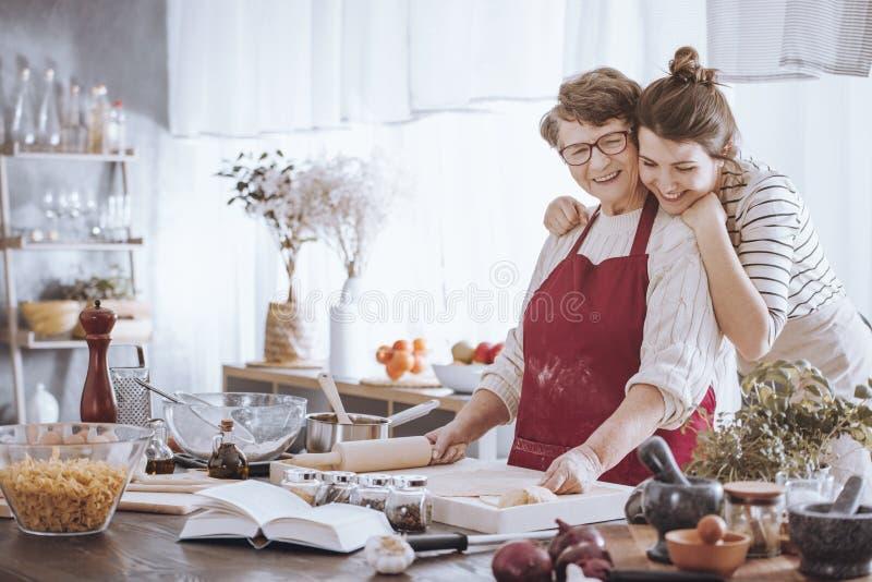 拥抱祖母的孙女在厨房里 免版税图库摄影