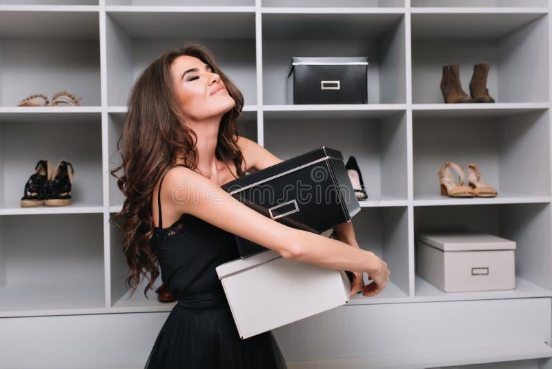 拥抱箱鞋子的俏丽的年轻女人在时髦的化装室,衣橱附近 她是非常愉快的,喜悦,关闭了 免版税库存图片