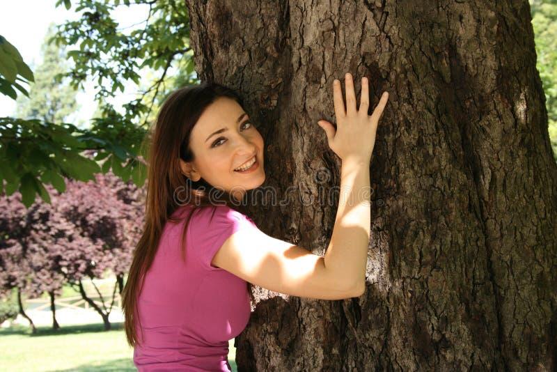拥抱结构树的庭院女孩 免版税库存图片