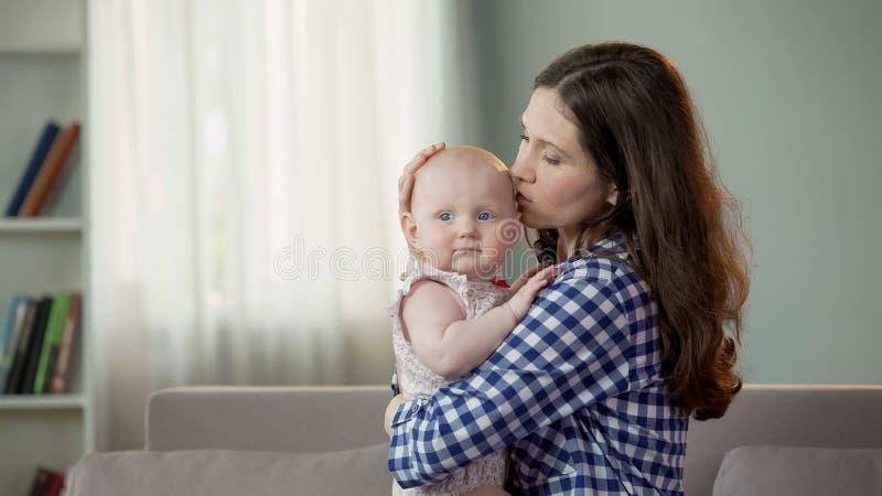 拥抱美丽的年轻的母亲亲吻逗人喜爱的小女儿和,愉快的未来 免版税库存照片