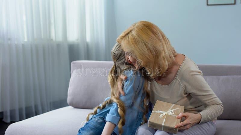 拥抱老婆婆和给她的礼物,家庭假日的俏丽的女性孙 库存图片