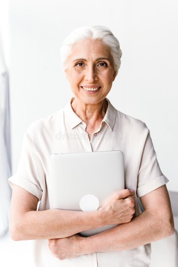 拥抱膝上型计算机的愉快的成熟的商业妇女 库存图片