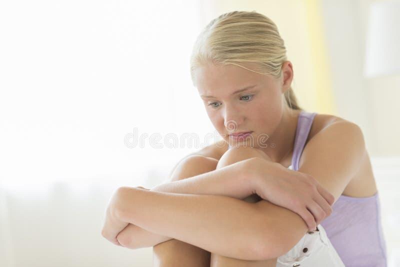 拥抱膝盖的沮丧的十几岁的女孩 库存图片