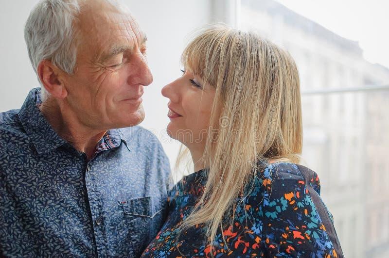 拥抱英俊的老人和看他的可爱的白肤金发的妇女充满爱和激情在她的眼睛 加上年龄 库存照片