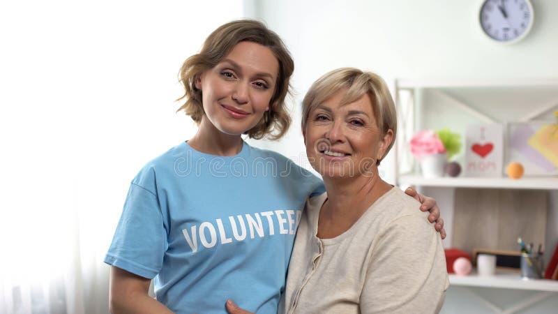 拥抱资深夫人,领抚恤金者援助计划,支持的女性志愿者 库存图片