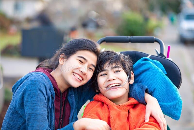 拥抱轮椅的姐姐残疾兄弟户外,微笑 免版税库存图片