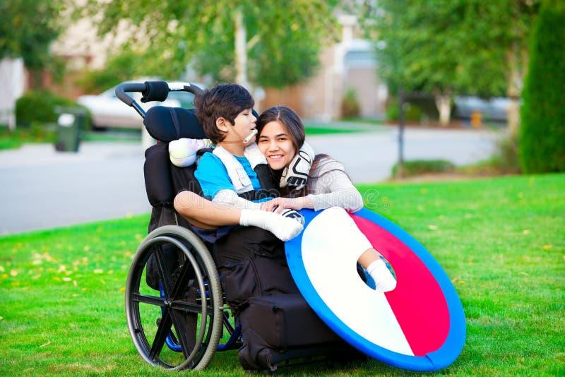 拥抱轮椅的残疾兄弟更老的姐妹户外 库存照片