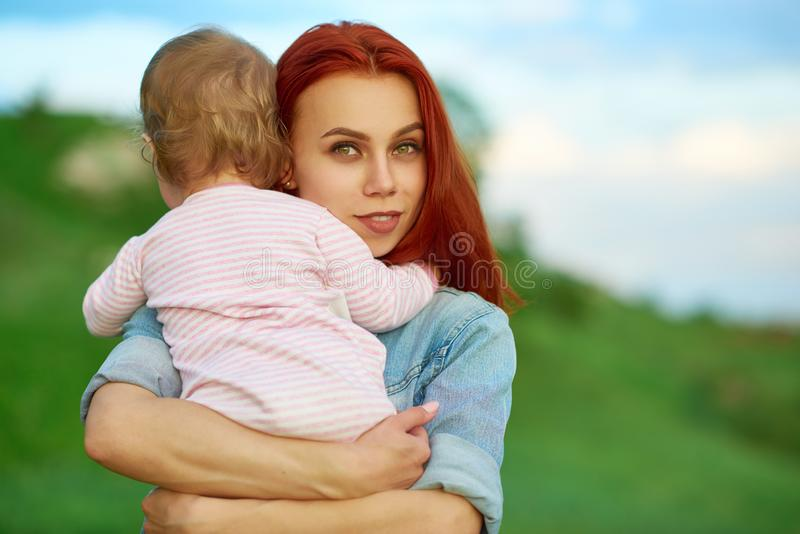 拥抱逗人喜爱的小孩的年轻母亲摆在绿色领域 图库摄影
