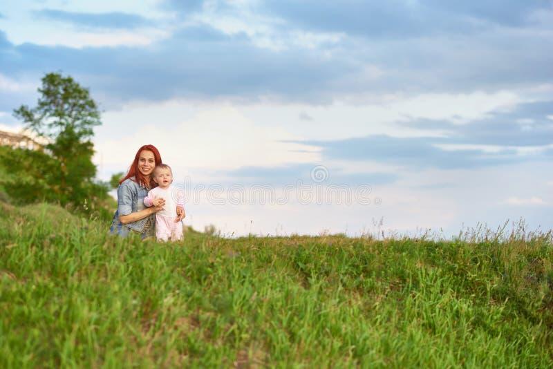 拥抱逗人喜爱的矮小的女儿的年轻母亲坐在领域的草 免版税库存照片
