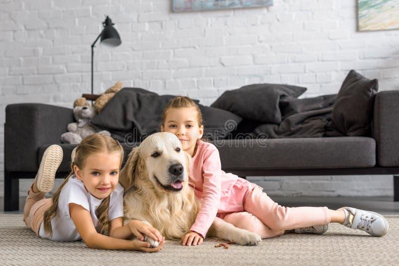 拥抱金毛猎犬狗的可爱的孩子,当坐地板时 免版税库存照片