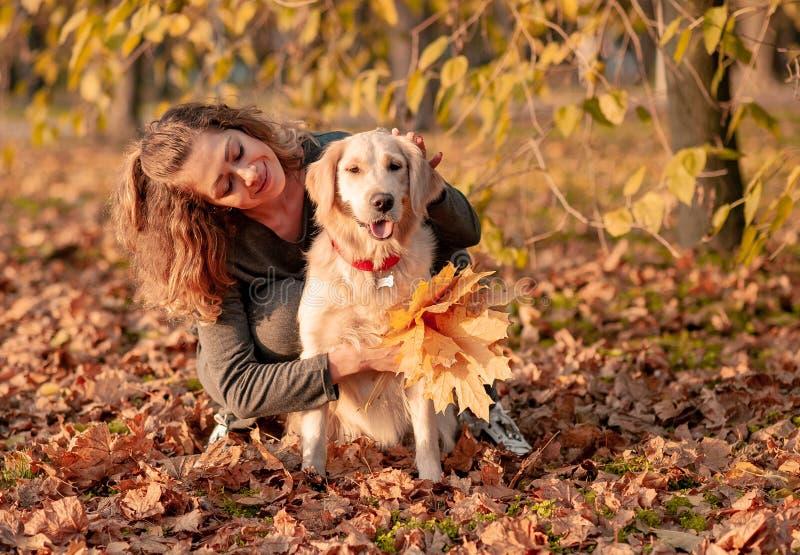 拥抱金毛猎犬狗的年轻美女 免版税库存图片